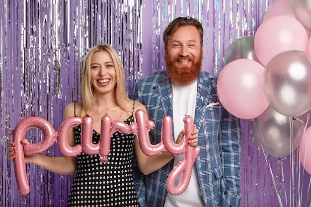 Geïsoleerde shot van gelukkige blonde vrouw in polka dot jurk, vrolijke roodharige man in formeel pak, luchtballonnen vasthouden, dicht staan