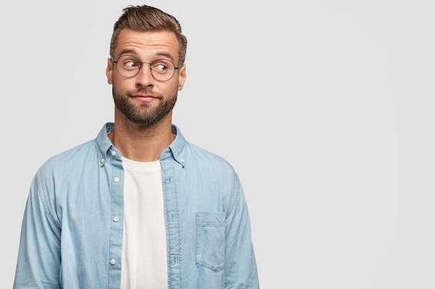 Geïsoleerde shot van grappige bebaarde man poseren tegen de witte muur
