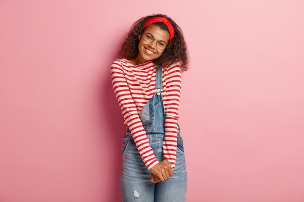 Geïsoleerde shot van het verlegen tienermeisje poseren in overall met krullend haar