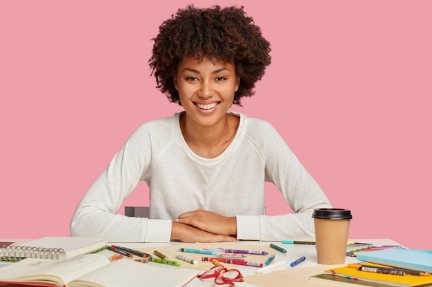 Geïsoleerde shot van hilarische vrouw met donkere huid heeft afro-kapsel, gekleed in een casual witte trui, zit op het bureaublad met creatieve chaos, drinkt afhaalkoffie, gebruikt kleurpotloden, heeft brede glimlach op het gezicht