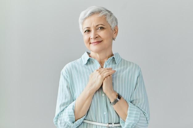 Geïsoleerde shot van mooie emotionele volwassen europese dame met pixiekapsel hand in hand op haar borst, gevuld met zalige emoties. houd van vriendelijkheid, dankbaarheid, erkenning en waardering concept