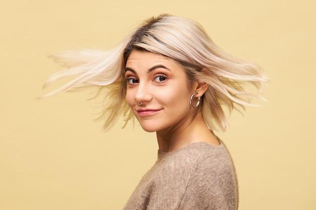 Geïsoleerde shot van mooie geweldige jonge vrouw in stijlvolle oversized trui draaien met blonde haren stroomt in de wind