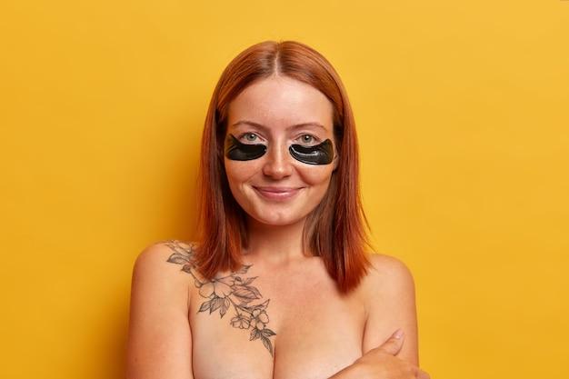 Geïsoleerde shot van mooie roodharige vrouw draagt zwarte collageen patches tegen rimpels en droge huid, ondergaat cosmetische ingrepen in de schoonheidssalon, staat blote schouders, geïsoleerd over gele muur