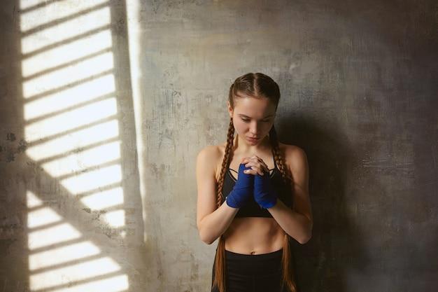 Geïsoleerde shot van mooie serieuze jonge europese vrouw professionele kickbokser met twee vlechten die handwraps en stijlvolle sport-outfit dragen