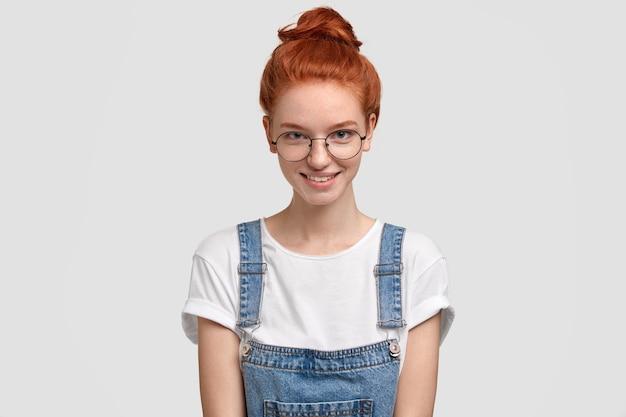 Geïsoleerde shot van mooie sproeten tienermeisje in denim overall, ronde optische bril, glimlacht positief