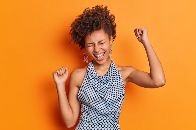 Geïsoleerde shot van mooie vrouw heeft plezier lacht van vreugde gekleed in modieuze kleding houdt gebalde vuisten geïsoleerd over levendige oranje muur geniet van vrijheid en onafhankelijkheid