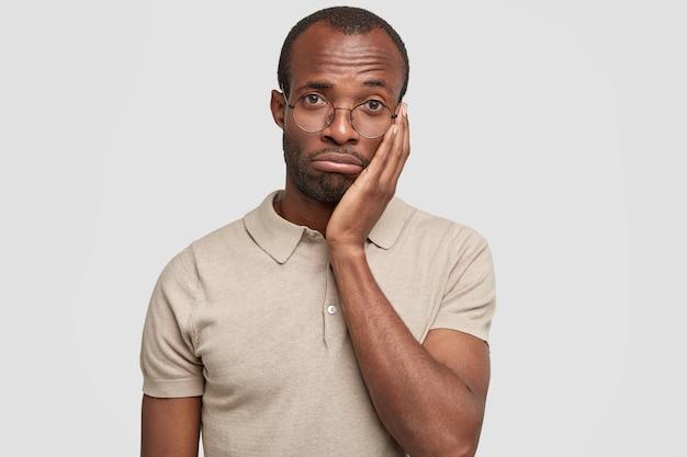 Geïsoleerde shot van ongelukkig african american man portemonnees lippen en kijkt wanhopig naar de camera