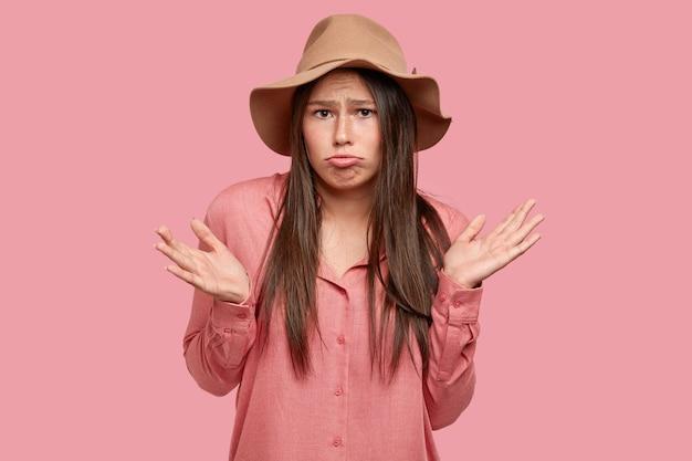 Geïsoleerde shot van ontevreden brunette vrouw portemonnees lippen, kan niet de juiste beslissing nemen
