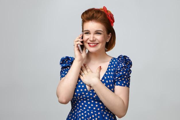 Geïsoleerde shot van prachtige emotionele jonge europese vrouw, gekleed in elegante vintage kleding, gelukkig lachend, hand op haar borst,