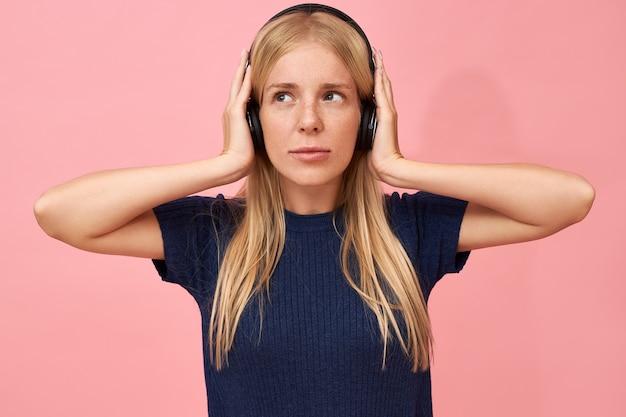 Geïsoleerde shot van schattige tiener meisje hand in hand op de oren, genietend van hoge kwaliteit muzieknummers in mp3-speler met behulp van draadloze hoofdtelefoon