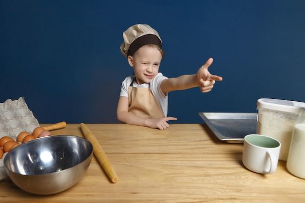 Geïsoleerde shot van speels schattig mannelijk kind in schort en hoed knipogen