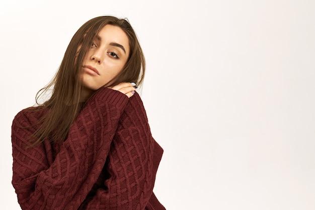 Geïsoleerde shot van stijlvolle schattige jonge vrouw die bevriest van de kou omdat de verwarming is uitgeschakeld, probeert op te warmen in een gebreide trui, zichzelf knuffelt