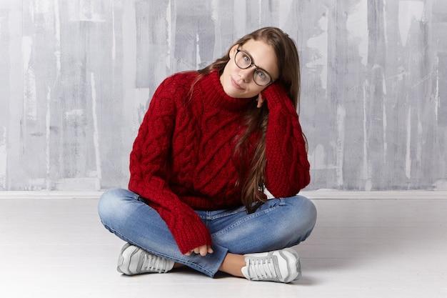 Geïsoleerde shot van stijlvolle tienermeisje in trendy hardloopschoenen, denim broek, gebreide trui en brillen die benen kruisen terwijl ze op de vloer zit, het hoofd naar de zijkant kantelt en haar lange losse haar aanraakt