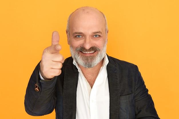 Geïsoleerde shot van succesvolle positieve vriendelijke senior zaken man in formele elegante kleding glimlachend wijzende vinger naar de camera, u rekruteren, positie in zijn bedrijf aanbieden. lichaamstaal