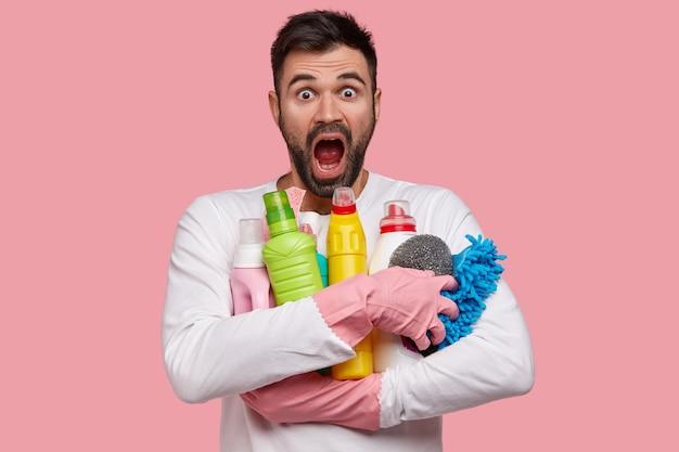 Geïsoleerde shot van verbijsterde bebaarde emotionele man draagt flessen wasmiddel op de voet, staart met een ongelooflijke uitdrukking, nonchalant gekleed