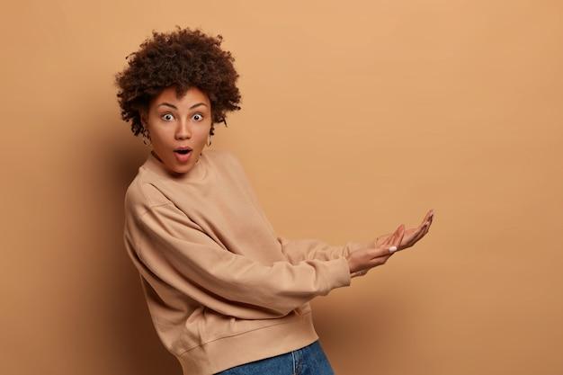 Geïsoleerde shot van verrast jonge afro-amerikaanse vrouw doet alsof ze iets groots vangt, handpalmen houdt, onzichtbaar object van onderaf vasthoudt, gekleed in een casual sweatshirt, geïsoleerd op een beige muur.
