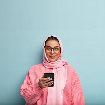 Geïsoleerde shot van vrij dromerige moslimvrouw gebruikt mobiele telefoon voor het verzenden van berichten in sociale netwerken, naar boven gericht, denkt na over de inhoud van het bericht, staat over de blauwe muur.