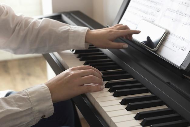 Geïsoleerde smartphone-scherm in vrouwelijke handen in de buurt van de piano