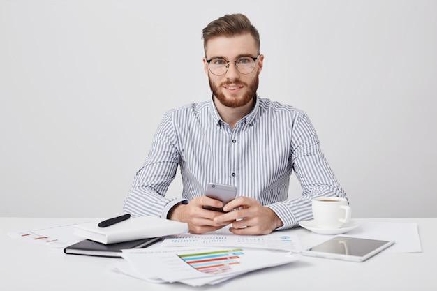 Geïsoleerde stdio shot van aangenaam uitziende stijlvolle mannelijke manager met stoppels, houdt slimme telefoon als berichten online