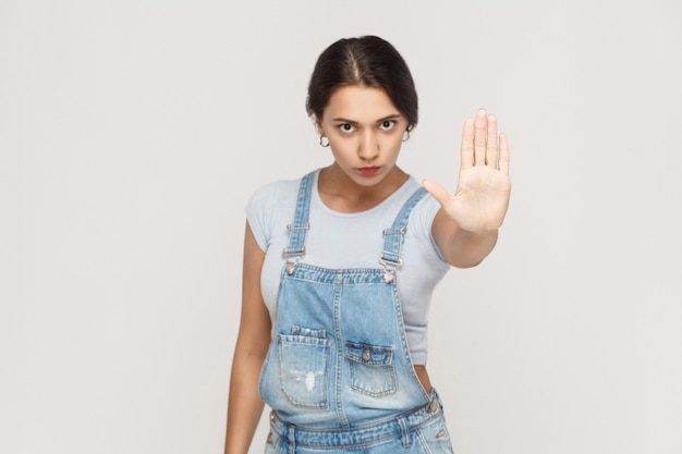 Geïsoleerde studio die op grijze achtergrond is ontsproten. jonge geërgerde vrouw met een slechte houding die een stopgebaar maakt met haar handpalm naar buiten, nee zegt, ontkenning of beperking uitdrukt.