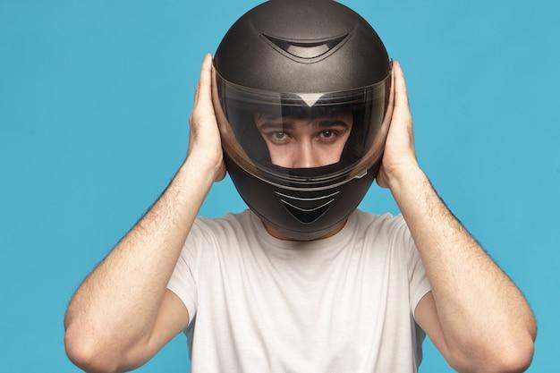 Geïsoleerde studio shot van zelfbepaalde serieuze jonge blanke mannelijke fietser nemen stijlvolle zwarte motorhelm