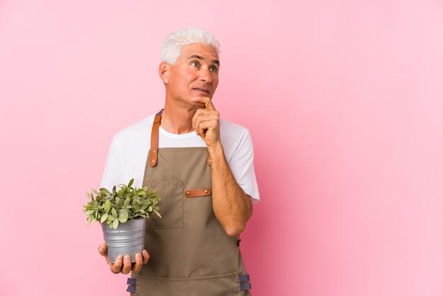 Geïsoleerde tuinman man van middelbare leeftijd opzij kijken met twijfelachtige en sceptische uitdrukking.
