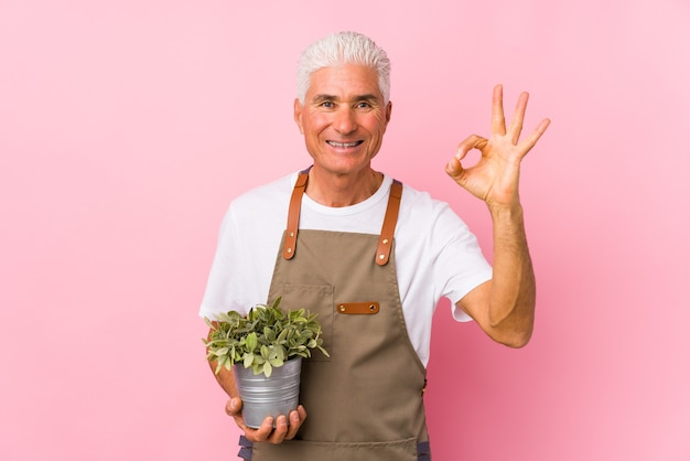 Geïsoleerde tuinman man van middelbare leeftijd vrolijk en vol vertrouwen ok gebaar tonen.
