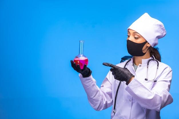 Geïsoleerde verpleegster in de hand en gezichtsmasker houdt chemische kolf vast en wijst ernaar met de vinger.