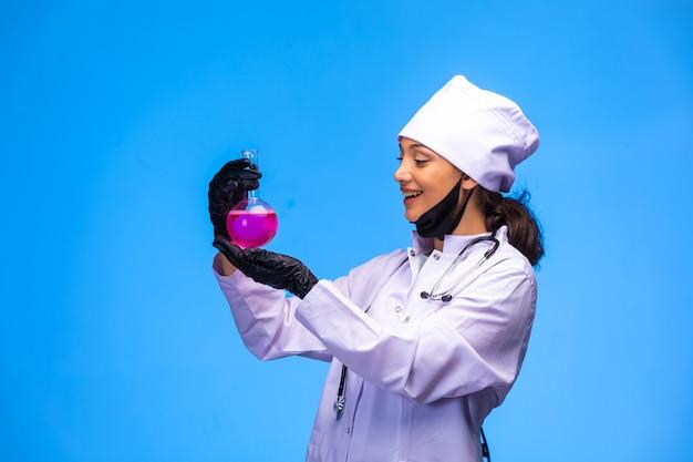 Geïsoleerde verpleegster in hand en gezichtsmasker toont kolf met roze vloeistof en glimlacht.