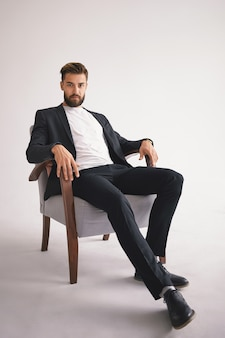 Geïsoleerde verticaal portret van succesvolle knappe stijlvolle jonge europese mannelijke baas met fuzzy bijgesneden baard dragen trendy herenkleding ontspannen in fauteuil en staren met serieuze blik