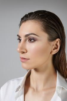 Geïsoleerde verticale weergave van modieuze stijlvolle jonge brunette vrouw met mannetje omhoog en donker haar achterover gekamd poseren, gekleed in zijde wit overhemd. schoonheid, stijl, huid en haarverzorging concept