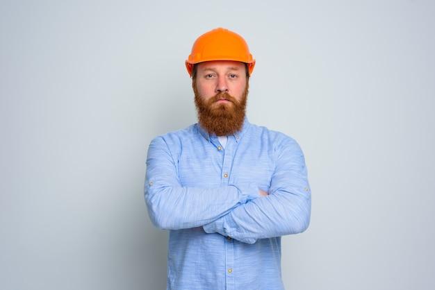 Geïsoleerde vertrouwensarchitect met baard en oranje helm