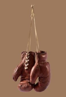 Geïsoleerde vintage bokshandschoenen die tegen bruin hangen