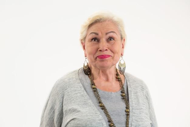 Geïsoleerde vrouw die senior vrouw op een witte achtergrond opzoekt, probeert positief te denken