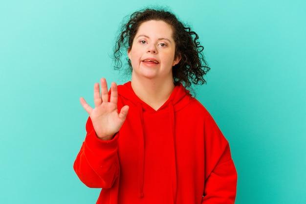 Geïsoleerde vrouw met het syndroom van down glimlachend vrolijk tonend nummer vijf met vingers