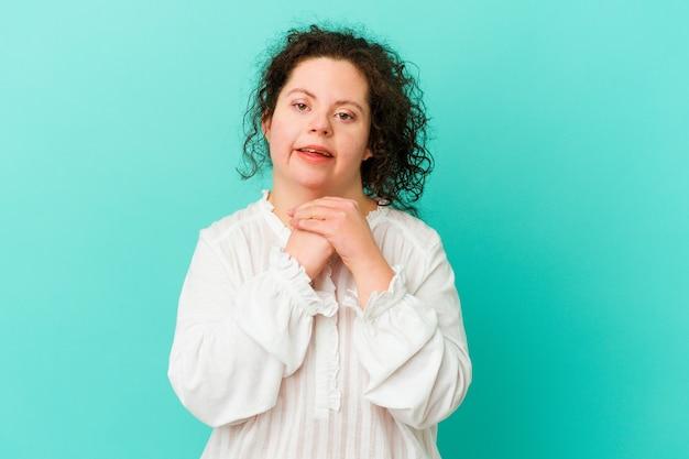 Geïsoleerde vrouw met het syndroom van down houdt de handen onder de kin, kijkt vrolijk opzij.