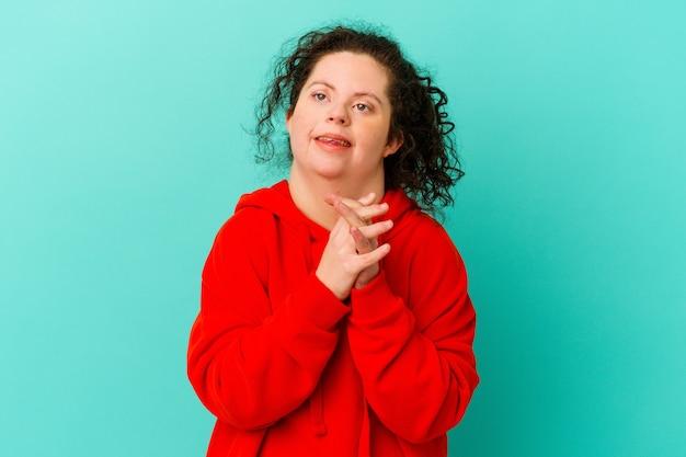 Geïsoleerde vrouw met het syndroom van down houdt handen onder de kin, kijkt vrolijk opzij