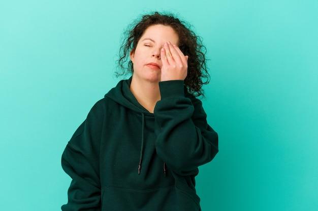 Geïsoleerde vrouw met het syndroom van down met hoofdpijn, de voorkant van het gezicht aanraken.
