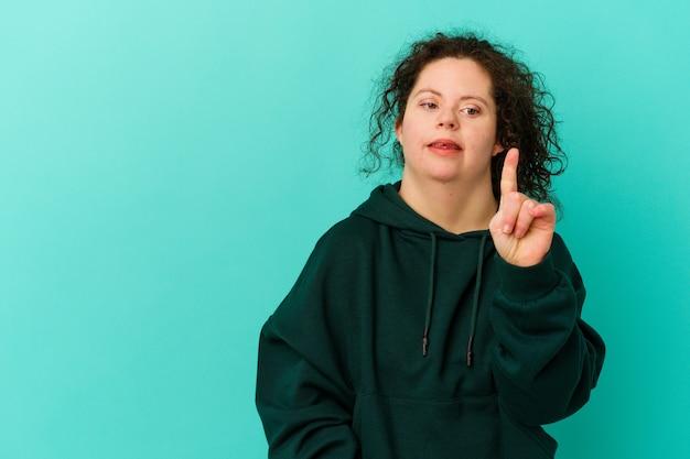 Geïsoleerde vrouw met het syndroom van down met nummer één met vinger