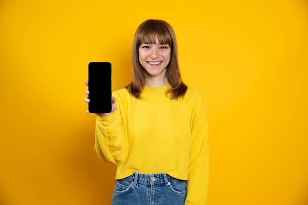 Geïsoleerde vrouw op een gele achtergrond met lege scherm mobiele telefoon