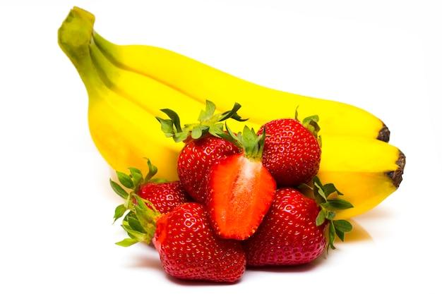 Geïsoleerde vruchten. bos van bananen en stapel van aardbeien die op witte achtergrond worden geïsoleerd