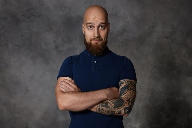 Geïsoleerde weergave van kale blanke hipster man met dikke borstelige baard en tatoeage wenkbrauwen optrekken, armen kruisen op de borst, zijn gesloten houding en blik wantrouwen uiten. lichaamstaal