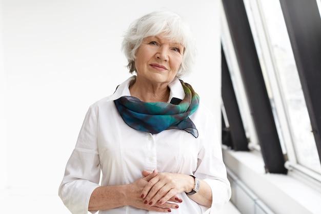 Geïsoleerde weergave van succesvolle positieve mooie zakenvrouw met grijs haar staande in zelfverzekerde houding