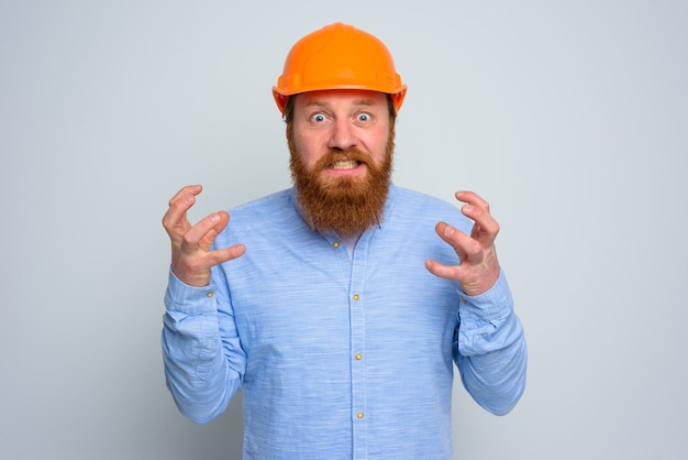 Geïsoleerde woedearchitect met baard en oranje helm