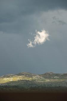 Geïsoleerde wolk verlicht door de zon in het midden van de storm