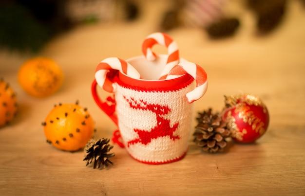 Geïsoleerde wollen stoffen mok met geborduurd hert op de houten tafel mok met mandarijnen en een snoepje