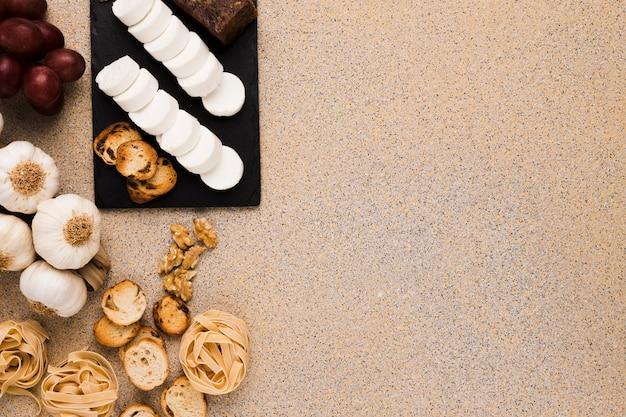 Geitenkaasplakken en brood op zwarte leisteen met ruw voedsel over geweven marmer