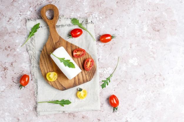 Geitenkaasplakken op houten bord met rucola, cherry tomaten. klaar om te eten.