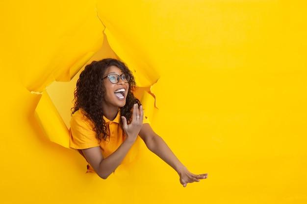 Gek blij wijzende vrolijke afro-amerikaanse jonge vrouw in gescheurd geel papier