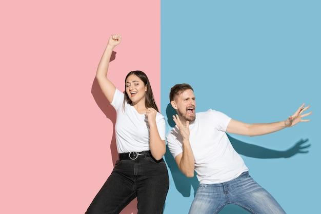 Gek. dansen, bewegen, plezier maken. jonge en gelukkige man en vrouw in vrijetijdskleding op roze, blauwe tweekleurige muur. concept van menselijke emoties, gezichtsuitdrukking, relaties, advertentie. mooi koppel.